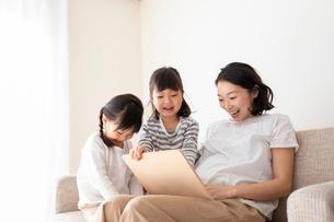 ソファーでくつろぐ母親と幼い姉妹の写真素材 [FYI01796480]
