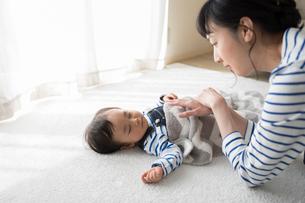 昼寝する赤ちゃんに添い寝する母親の写真素材 [FYI01796534]