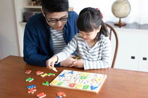 アルファベットのパズルをする女の子とそれを手伝う父親の写真素材 [FYI01796581]