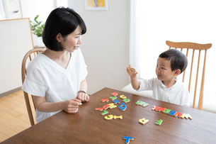 英語の知育玩具で英語の学習をする男の子とそれを手伝う母親の写真素材 [FYI01796661]