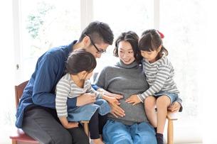 妊娠している母親のお腹を触る家族の写真素材 [FYI01796663]