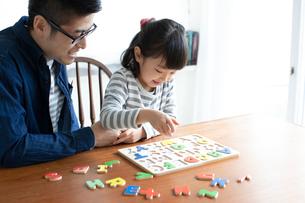 英語のパズルをする女の子とそれを手伝う父親の写真素材 [FYI01796669]