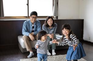 手をつないでリビングを歩く小さな姉妹とそれを後ろから見て微笑む両親の写真素材 [FYI01796672]