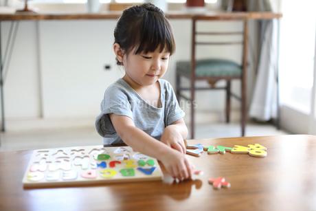 アルファベットのパズルをする女の子の写真素材 [FYI01796744]