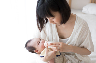 母親に抱かれながら哺乳瓶でミルクを飲む赤ちゃんの写真素材 [FYI01796765]
