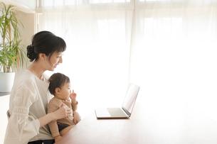 リビングルームで一緒にパソコンを見る赤ちゃんと母親の写真素材 [FYI01796790]