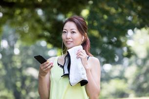 汗を拭きながらスマホを見るジョギング中の女性の写真素材 [FYI01796828]
