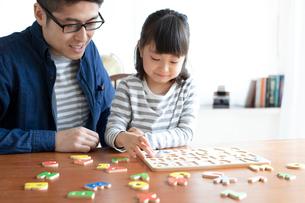 英語のパズルをする女の子とそれを手伝う父親の写真素材 [FYI01796837]