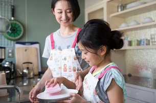 キッチンで食器洗いをするエプロンを付けた小学生の女の子と母親の写真素材 [FYI01796871]