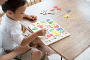 英語の知育玩具で英語の学習をする男の子とそれを手伝う母親の写真素材 [FYI01796887]