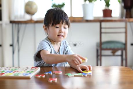 アルファベットのパズルをする女の子の写真素材 [FYI01796890]