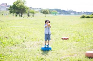 水鉄砲を持って遊具の上に立つ男の子の写真素材 [FYI01796896]