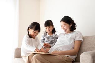 ソファーでくつろぐ母親と幼い姉妹の写真素材 [FYI01796964]