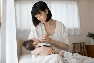 寝室で赤ちゃんに哺乳瓶でミルクを飲ませる母親の写真素材 [FYI01797023]