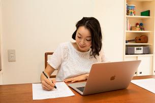 ノートパソコンで仕事をしながら書類に記入する女性の写真素材 [FYI01797283]