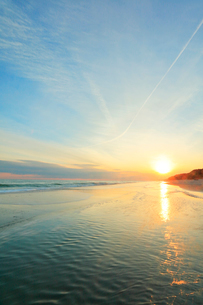 浜辺に寄せる波と夕日に飛行機雲の写真素材 [FYI01799277]