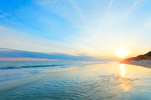 浜辺に寄せる波と夕日に飛行機雲の写真素材 [FYI01799306]