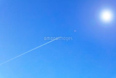 青空に飛行機雲と太陽の写真素材 [FYI01799931]