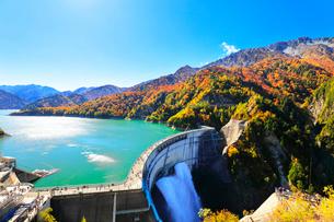 秋の立山 黒部ダム観光放水と紅葉の山並みの写真素材 [FYI01799981]