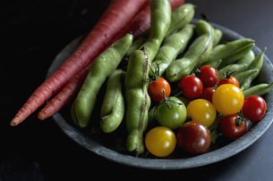 お盆に盛り付けた洗ったばかりのいろいろな野菜の写真素材 [FYI01800041]
