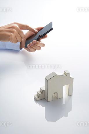スマートフォンとミニチュアの家の写真素材 [FYI01800706]