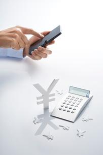 スマートフォンと電卓と通貨マークの写真素材 [FYI01800719]