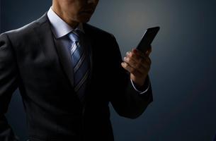 スマホを見るビジネスマンの写真素材 [FYI01800782]