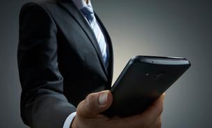 スマートホンを見るビジネスマンの写真素材 [FYI01800829]