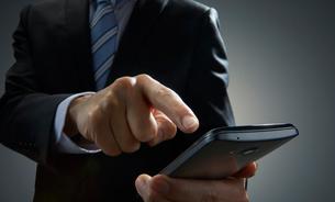 スマートホンをタッチするビジネスマンの写真素材 [FYI01800859]