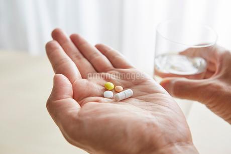 手のひらの薬とコップの写真素材 [FYI01800936]
