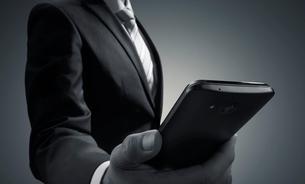 スマートホンを見るビジネスマンの写真素材 [FYI01800981]