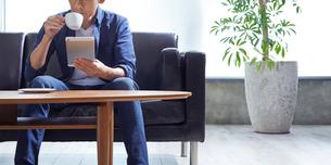 コーヒーを飲みながらタブレット端末を見る男性の写真素材 [FYI01800985]