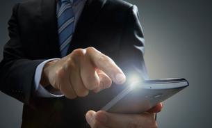スマートホンをタッチするビジネスマンの写真素材 [FYI01801022]