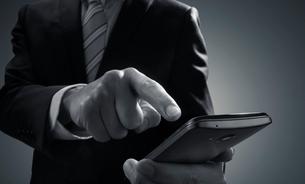 スマートホンをタッチするビジネスマンの写真素材 [FYI01801062]