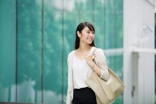 ビルの前を歩く女性の写真素材 [FYI01801351]