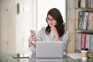 オフィスでノートパソコンを開き仕事をする女性の写真素材 [FYI01801368]