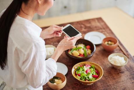 料理の写真を撮る女性の写真素材 [FYI01801379]