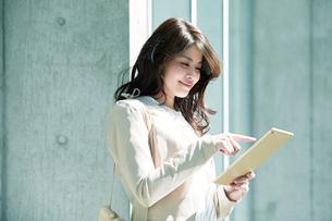 ビルの前に立ちタブレットPCを持つ女性の写真素材 [FYI01801419]