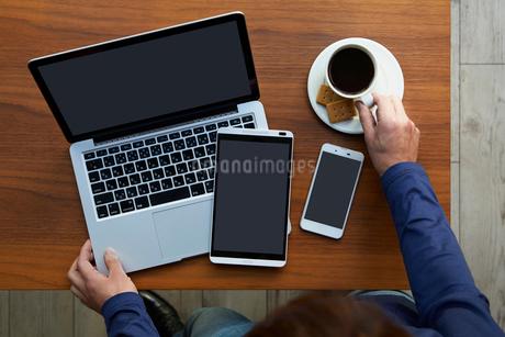 テーブルの上のモバイル端末と人物の写真素材 [FYI01801422]