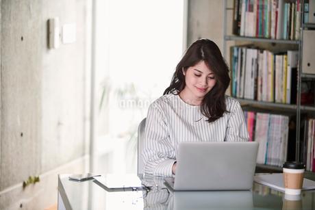 オフィスでノートパソコンを開き仕事をする女性の写真素材 [FYI01801431]