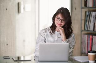オフィスでノートパソコンを開き仕事をする女性の写真素材 [FYI01801441]