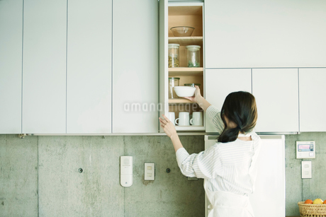 キッチンに立ち食器棚を開ける女性の写真素材 [FYI01801458]