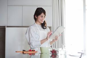 キッチンに立ちタブレットPCを持つ女性の写真素材 [FYI01801459]