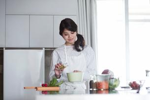 キッチンに立ち料理を作る女性の写真素材 [FYI01801460]