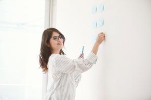 壁にふせんを貼る女性の写真素材 [FYI01801487]