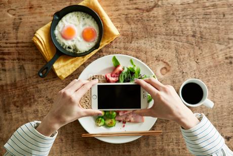 スマートフォンで料理の写真を撮る女性の写真素材 [FYI01801489]