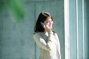 ビルの前に立ちスマートフォンを持つ女性の写真素材 [FYI01801544]