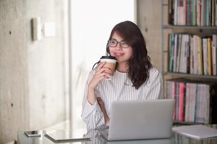 オフィスでノートパソコンを開き仕事をする女性の写真素材 [FYI01801554]