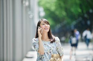 スマートフォンを持ち街を歩く女性の写真素材 [FYI01801566]