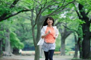 緑の中を走る女性の写真素材 [FYI01801569]